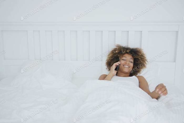 Smiling woman in bed having phone call