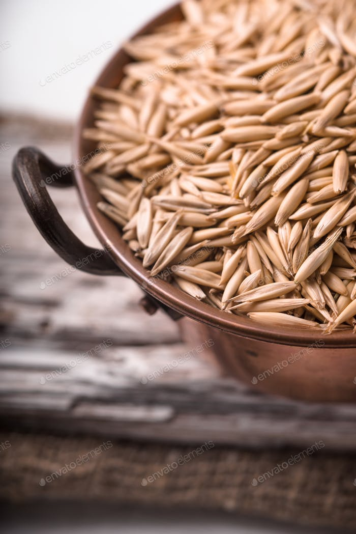 Oats in a copper bowl on a wooden stand closeup