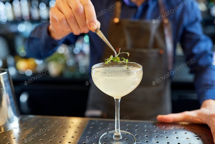 bartender decorating glass of cocktail at bar
