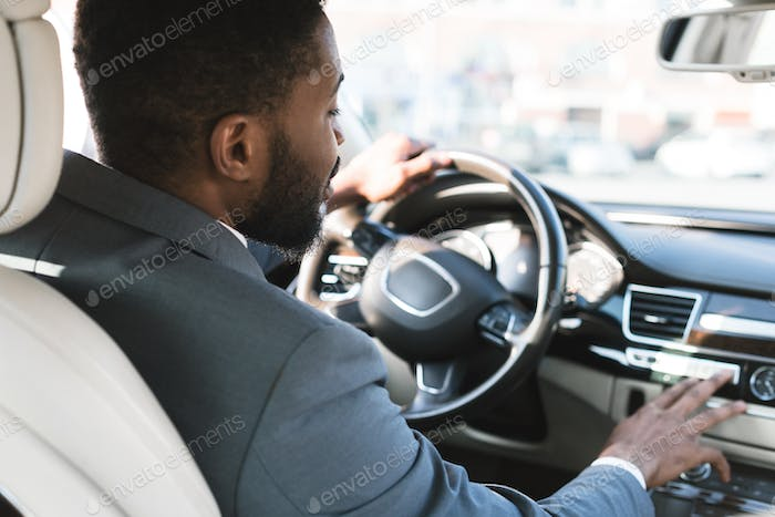 Driving with comfort. Businessman touching dashboard in car