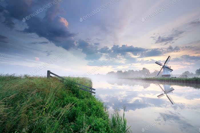 Dutch windmill by river at misty sunrise