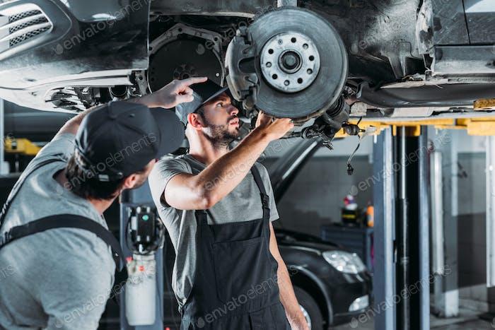 Automechaniker reparieren Auto ohne Rad in der Werkstatt
