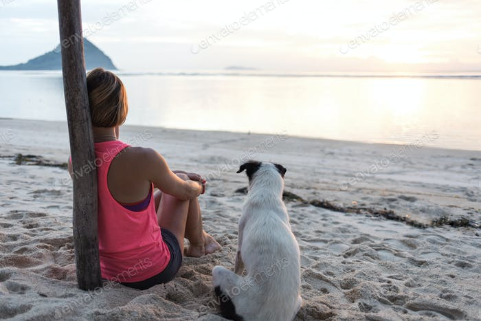 sporty woman or girl sitting with white dog