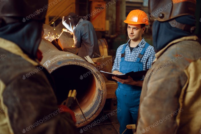 Master and crew of welders works on factory