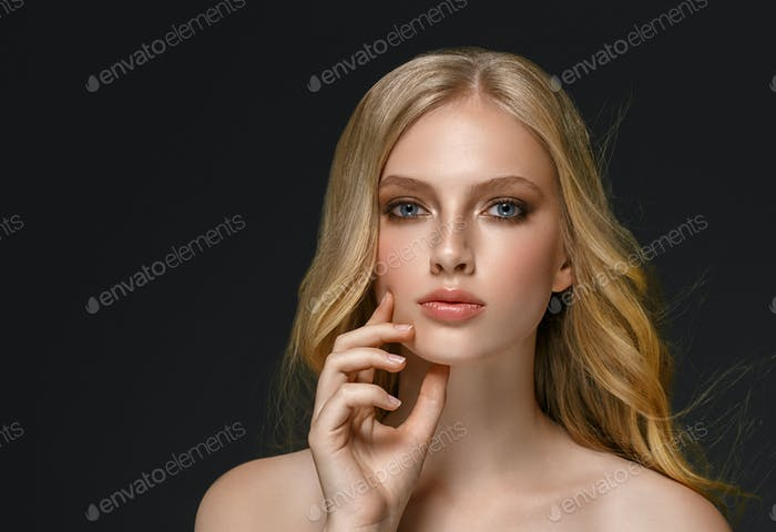 Long blonde hair model woman over black background film effect. Beauty concept.