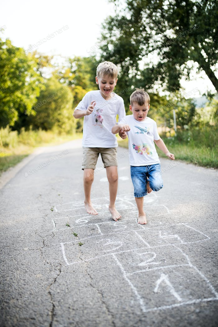 Two small boys hopscotching on a road in park on a summer day.