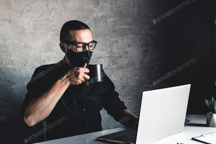 A masked man works at a computer. Pandemic, coronavirus, epidemic