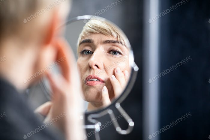 Middle-Aged Lady Looking In Mirror At Wrinkles In Bathroom Indoors