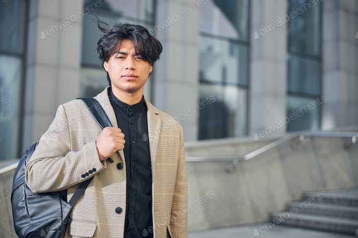 Good-looking young man standing on the street