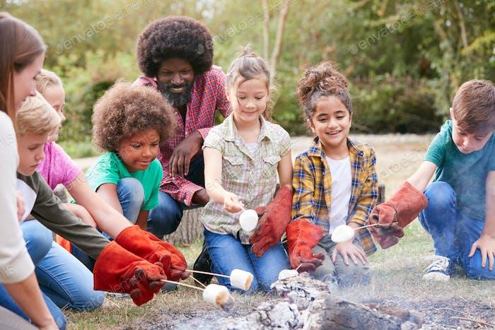 Teamleiter mit Gruppe von Kindern auf Outdoor-Aktivität Reise Toasten Marshmallows über Lagerfeuer