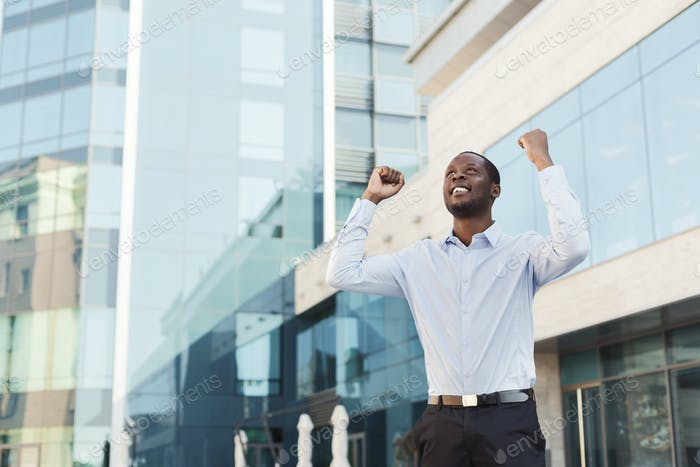 Happy excited businessman celebrate. Winner, black man outdoors