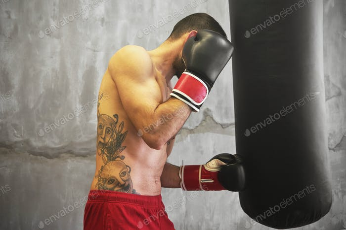 Boxer man doing exercise with punching bag