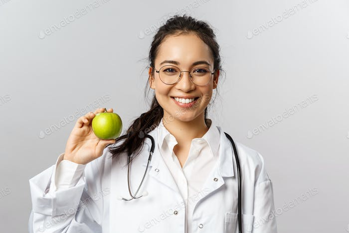 An apple a day keeps doctors away. Portrait of optimistic cute asian female doc in white coat