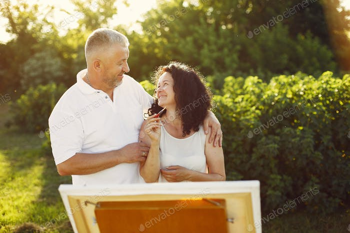 Beautiful adult couple drawing in a summer field