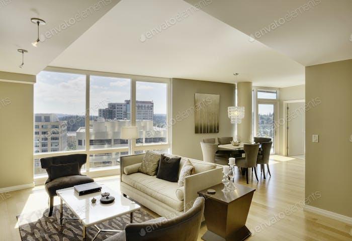 Sun shining through windows of open floor plan in luxury highrise apartment