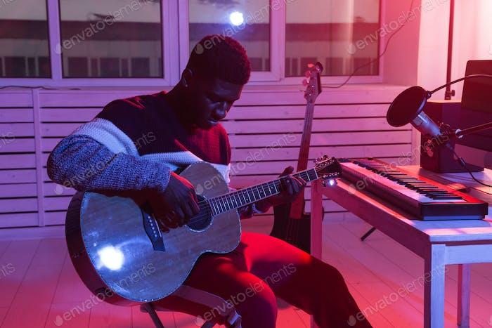 C African american man guitarist recording electric guitar track in home studio