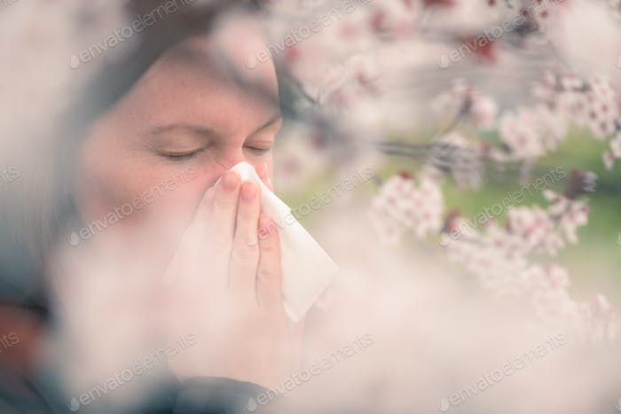 Woman sneezing in front of blooming cherry tree in spring