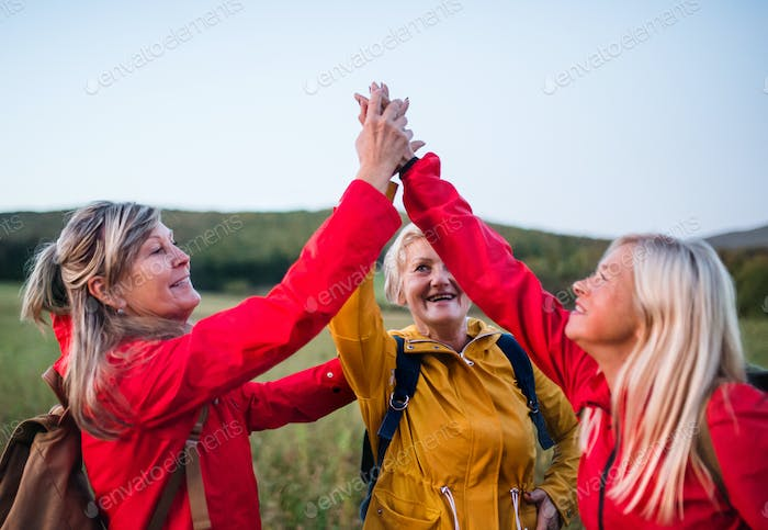 Senior women on walk outdoors in nature at dusk, giving high five