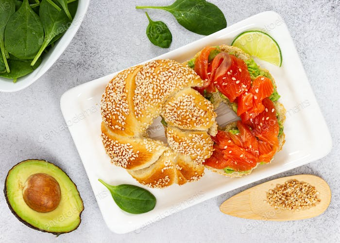 Sliced salmon with avocado on bagel with sesame seeds