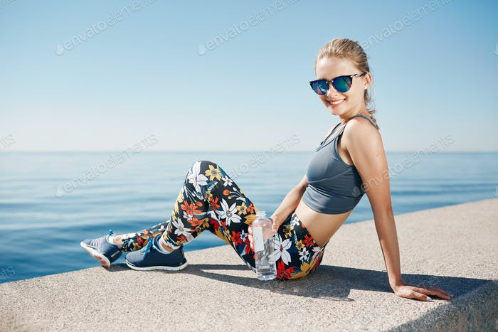 Young fitness blonde woman hold bottle water after fit at beach