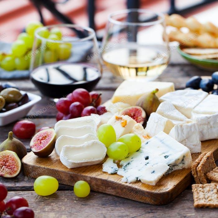 Käse- und Obstsortiment auf Schneidebrett mit rotem, weißem Wein auf Holzhintergrund. Leerzeichen kopieren.