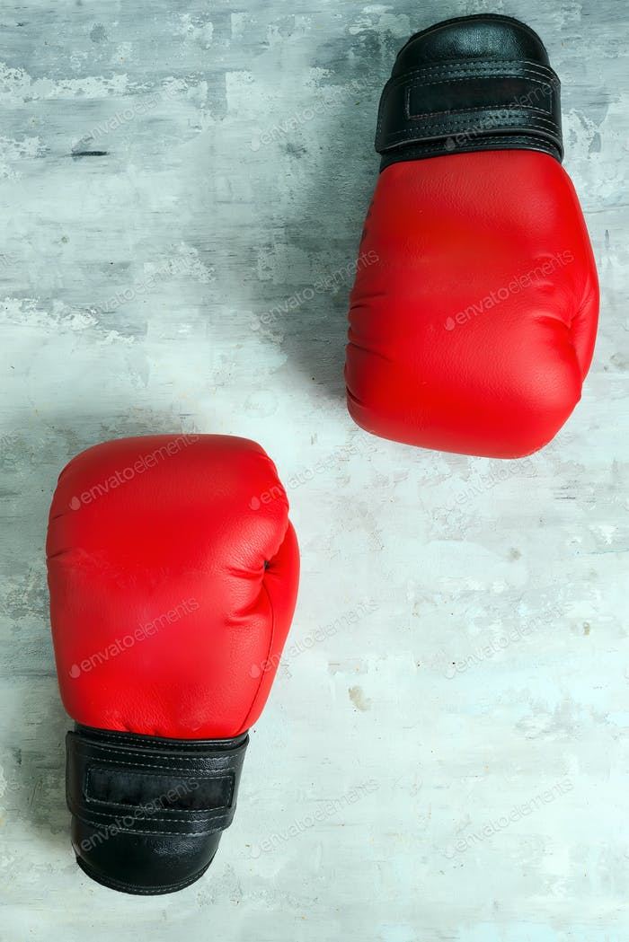 Пара красных боксерских перчаток на сером фоне