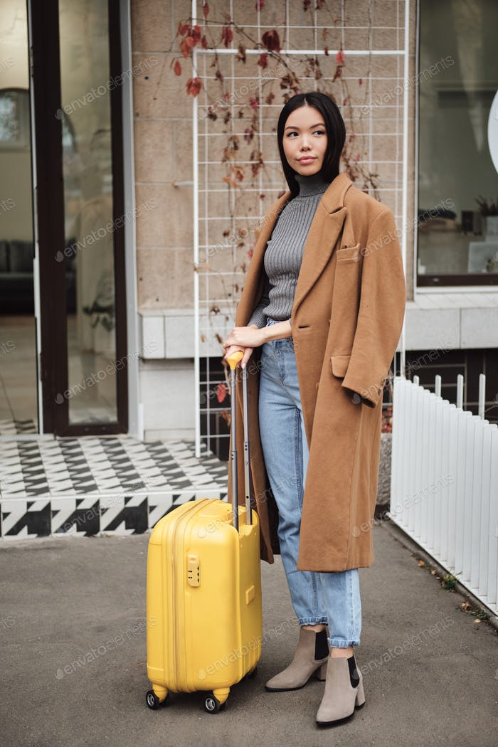 Beautiful stylish Asian girl in coat dreamily looking away standing with yellow suitcase on street