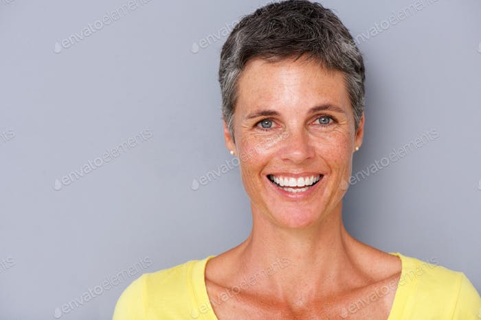 Close up attractive middle age woman smiling against gray background