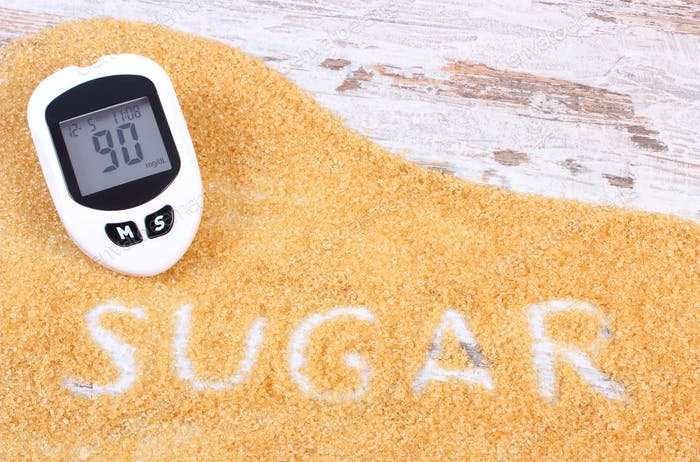 Glucometer for measurement sugar level and granulated brown cane sugar, concept of diabetes