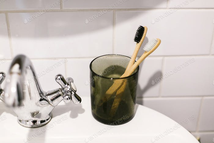 Zero waste bathroom concept. Eco natural bamboo toothbrushes in glass jar on sink in bathroom