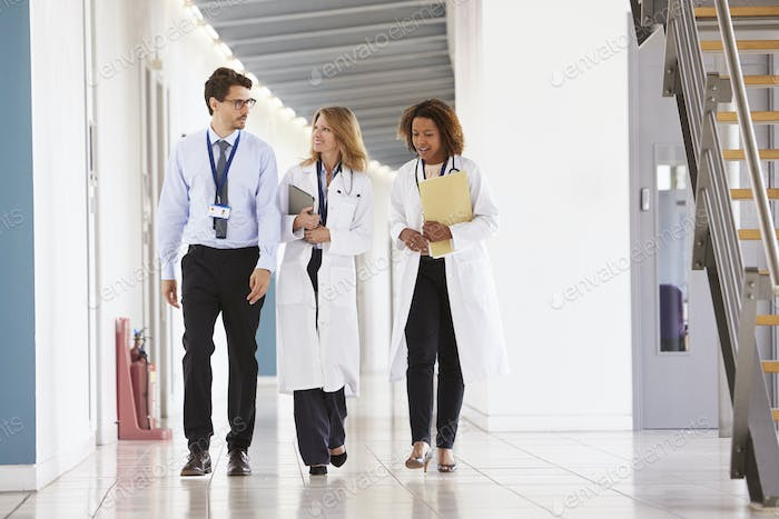 Three young male and female doctors walking in hospital