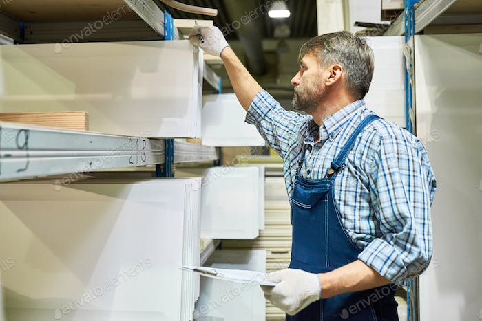 Mature Worker Doing Inventory in Storage Room
