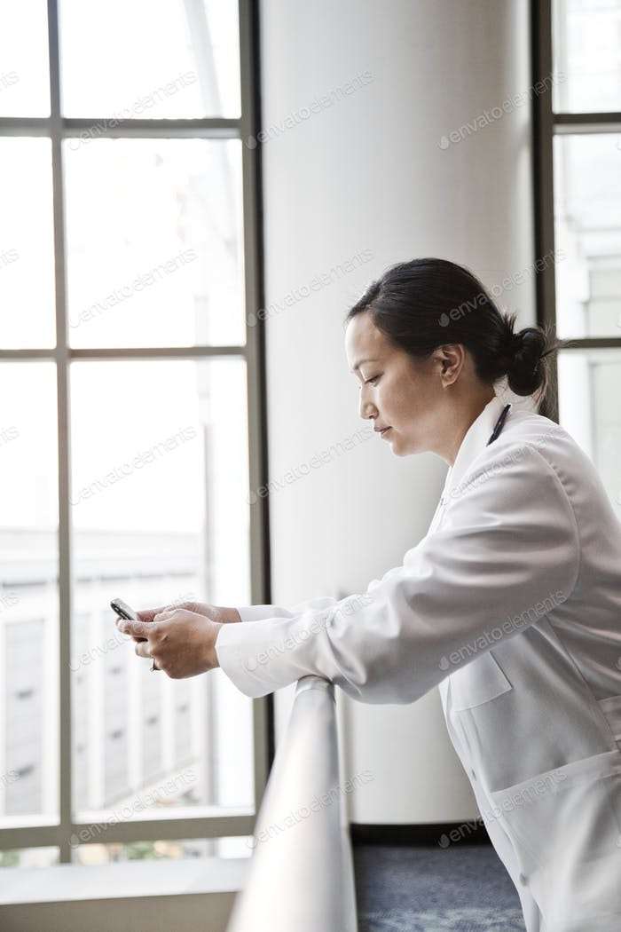 Asian woman doctor texting.
