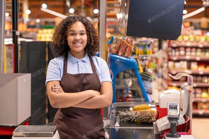 Ziemlich jung lächelnd afro-amerikanische Verkäuferin schaut dich an