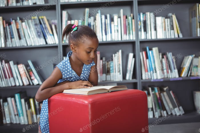 Girl reading book on ottoman in library