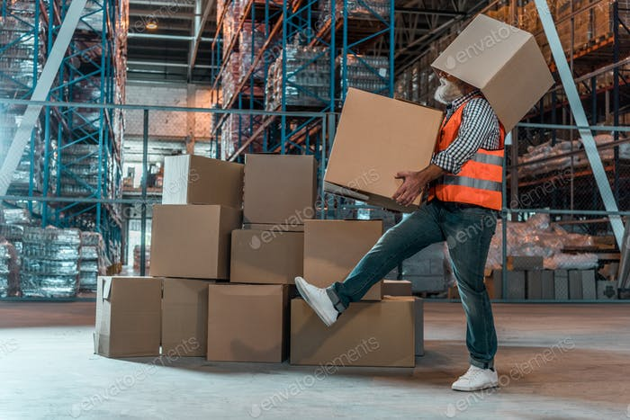 side view of bearded warehouse worker with boxes walking in storehouse