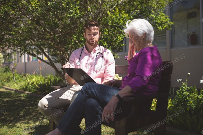 Male doctor showing medical reports to senior woman at backyard nursing home