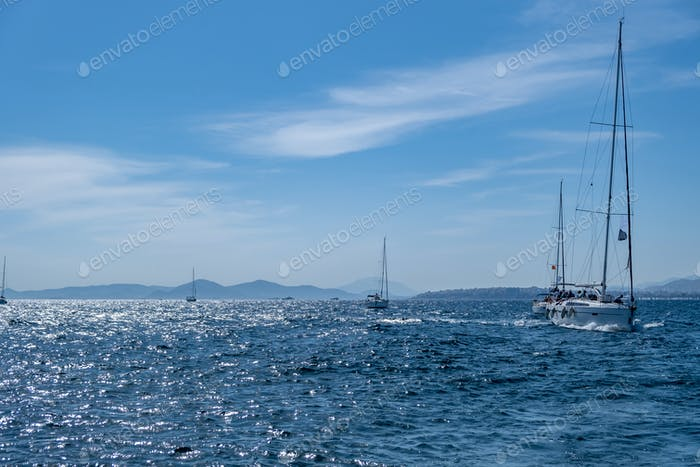 Sailing boats with open white sails, blue sky and rippled sea background