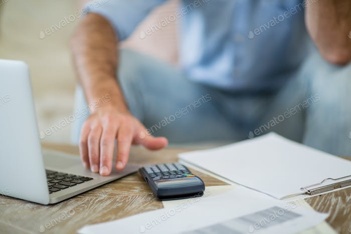 Man using laptop with bills on table in living room