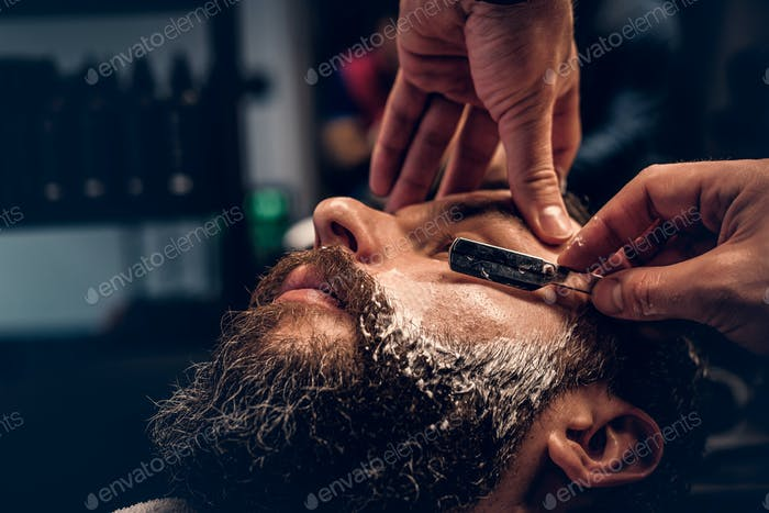Парикмахерская бритья бородатый мужчина с острой бритвой.