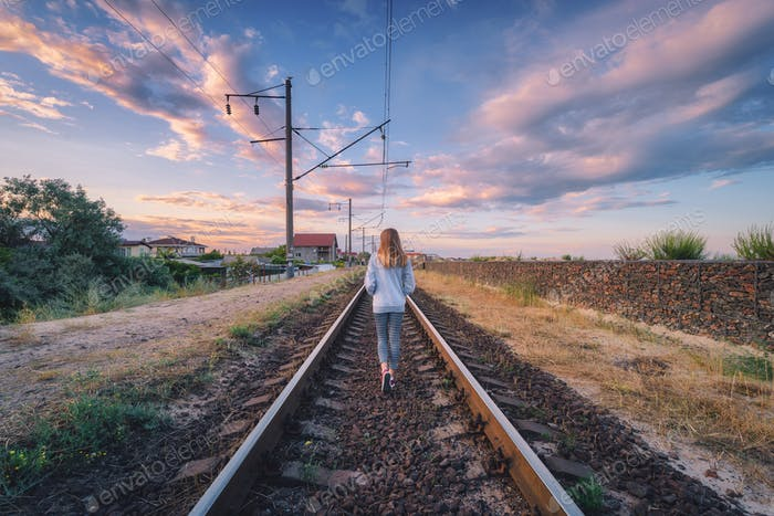 Standing young woman on the railroad at sunset in summer