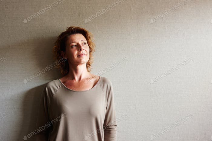 Woman with curly hair leaning on wall in contemplation