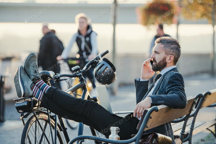 Businessman commuter with bicycle sitting on bench in city, making a phone call.