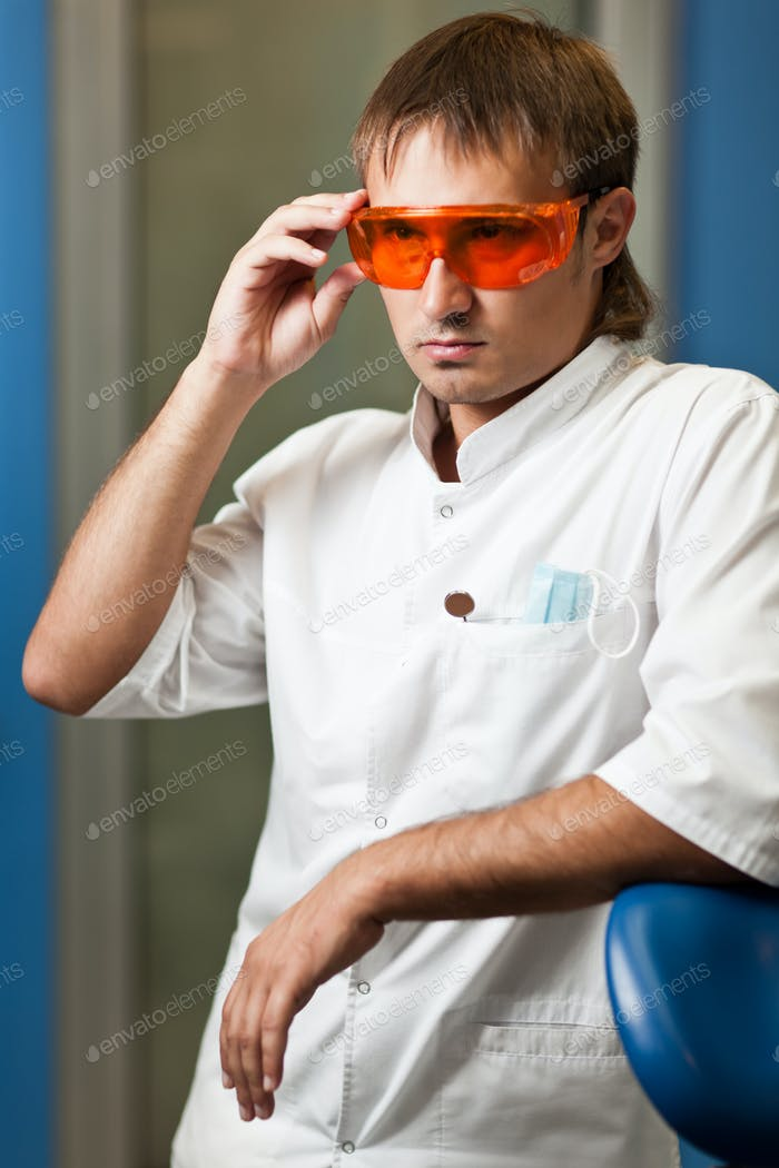 Young serious dentist doctor man in white traditional uniform and glasses standing in dental office