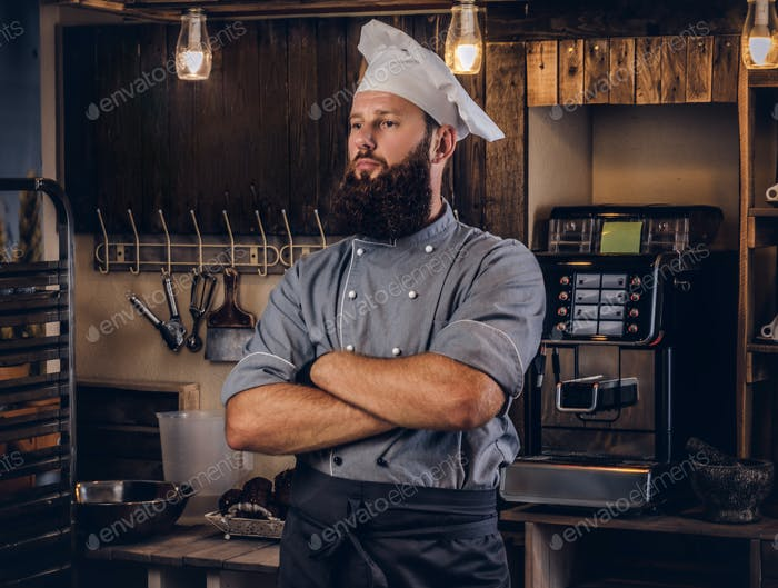 Professional baker in cook uniform posing with crossed arms near in bakery.