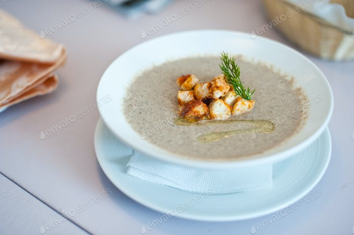 Cream soup with mushrooms champignon and potato in white bowl. Shallow depth of field
