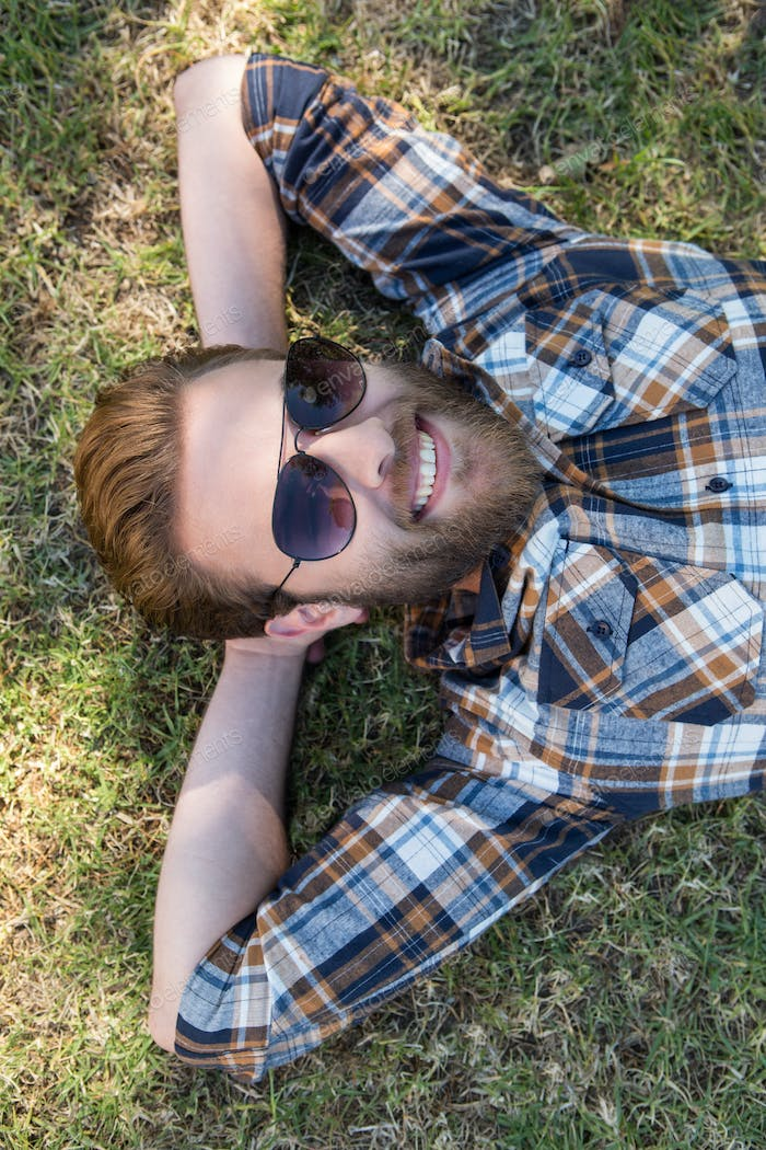Handsome hipster relaxing in the park on a summers day