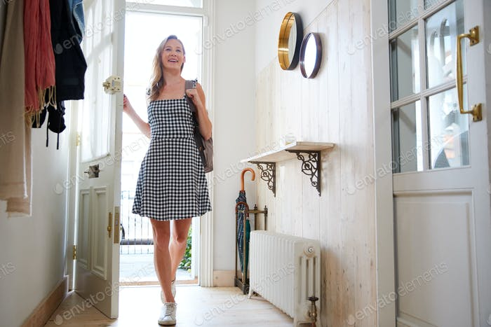 Woman Wearing Backpack Opening Front Door Coming Home From Work