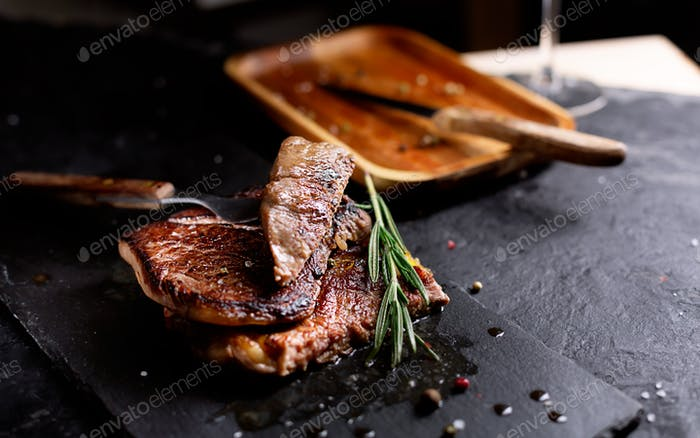 Pieces of Beef Steak on a dark plate with rosemary and pepper