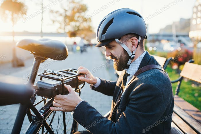 Hipster businessman commuter setting up electric bicycle in city.